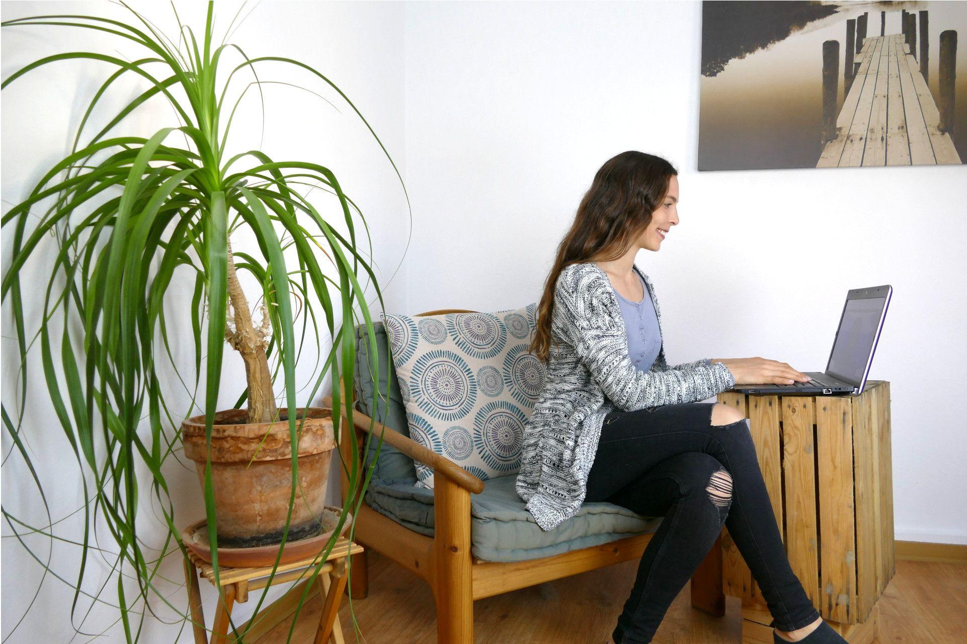 Stressmanagement und Psychologische Online Beratung: Anna sitzt auf einem Sessel, vor ihr steht ein Laptop, mit dem sie eine Psychologische Online Beratung durchführt. Sie lacht und ist glücklich, denn die Arbeit mit dem Klienten macht Spaß und erste Erfolge in der persönlichen Weiterentwicklung zeigen sich. Glücklicher und entspannter werden ist etwas, dass jeder verdient hat.