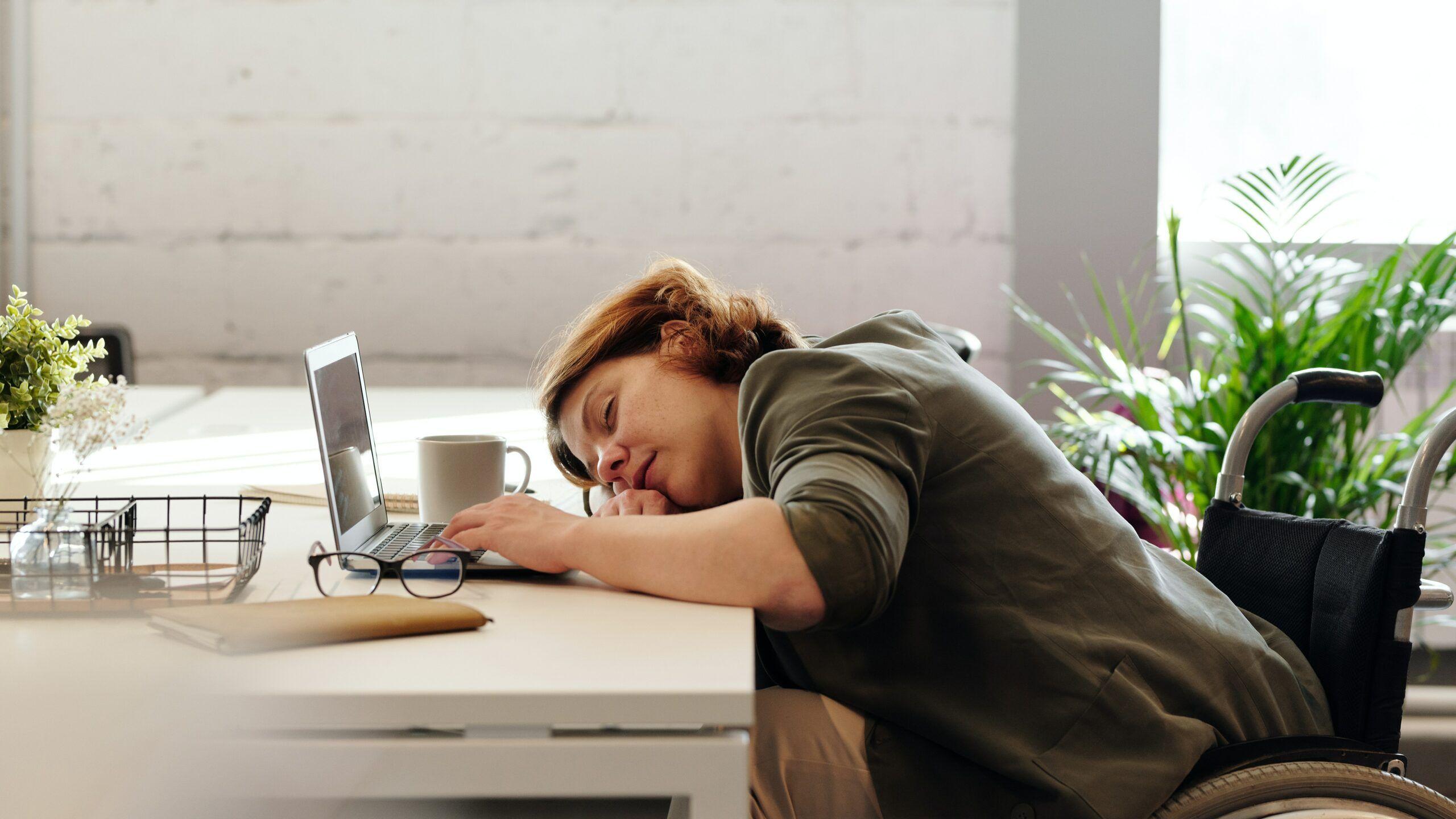 Erschöpfte junge Frau die auf ihrem Schreibtisch schläft.